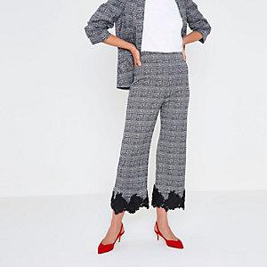 Jupe-culotte à carreaux noire avec dentelle à fleurs à l'ourlet