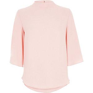 Roze hoogsluitende top met capemouwen