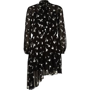 Zwarte jurk met zilverkleurige bloemenprint en strik in de nek.