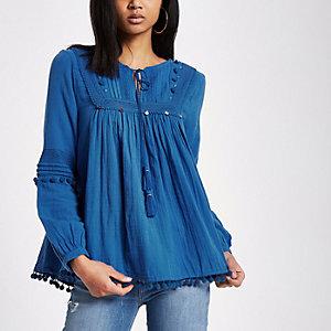 Blauwe top met pomponrand en kanten schouderstukken