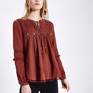 Donkerrode top met kanten schouderstuk, pompons en knoop in de hals