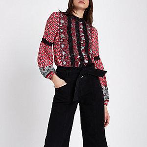 Rote, hochgeschlossene Bluse mit Kachelmuster und Spitzenbesatz