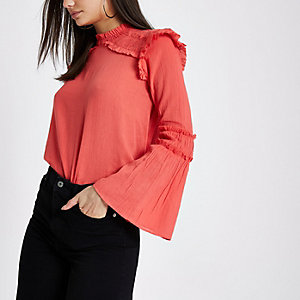 Koraalroze blouse met klokmouwen en ruches op de schouders