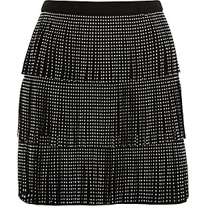 Mini jupe imitation daim noir à frange cloutée