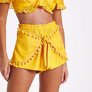 Gele strandshort met pompons en strik voor
