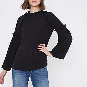 Zwarte hoogsluitende blouse met ruches en wijduitlopende mouwen