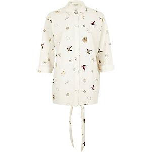 White jewellery and bird print shirt