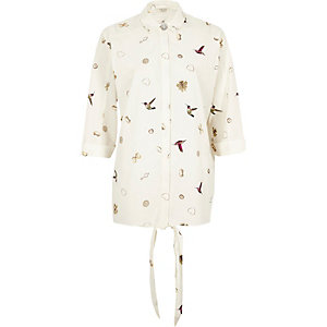 White jewelry and bird print shirt