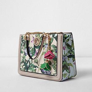 Crème handtas met bloemen- en bladerprint en bloemvormige versiering
