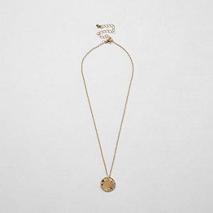 Goudkleurige ketting met verweerde schijf bezet met diamantjes