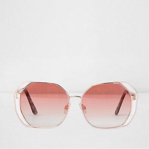 Rosegoudkleurige zonnebril met uitsnede en rode glazen