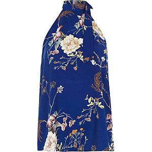 Blauwe haltertop met gekruiste bandjes op de rug en bloemenprint