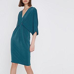 Blauwe midi-jurk met vleermuismouwen en gedraaide voorkant