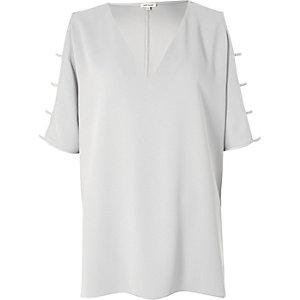 T-shirt gris à col en V et découpes aux manches