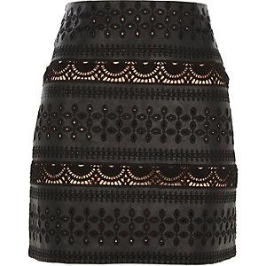 Mini-jupe en cuir synthétique noir à broderie