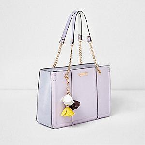 Lila-paarse handtas met bloemenbedeltje en ketting