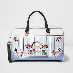 Blaue Reisetasche mit Streifen und Blumenmuster