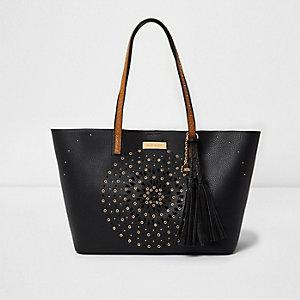Black laser cut eyelet stud tassel tote bag