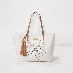White laser cut eyelet stud tassel tote bag