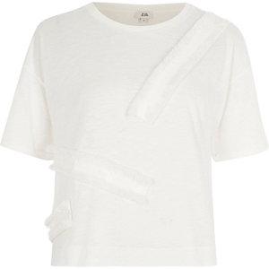 Crème ruimvallend T-shirt met biezen met franje