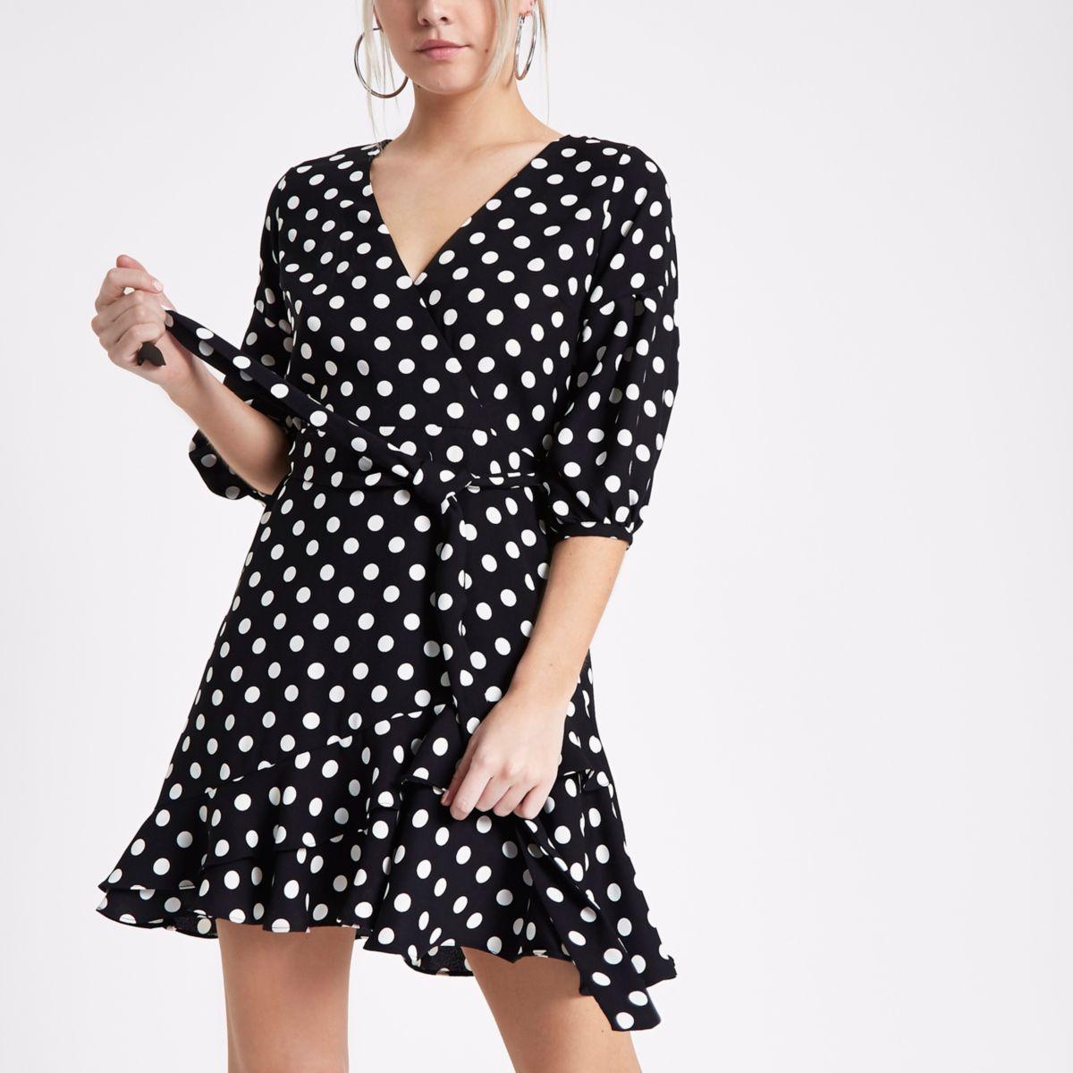 RI Petite - Zwarte gestippelde mini-jurk met overslag en ruches