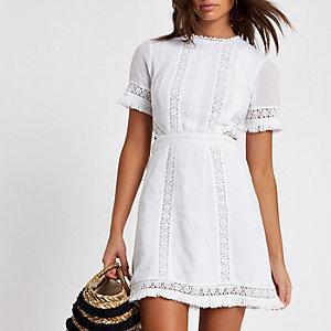 Witte mini-jurk met uitsnedes en gehaakte bies