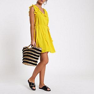 Gele korte swingjurk met vetersluiting op de rug en ruches
