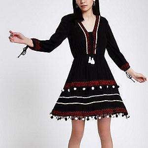 Schwarzes, gesmoktes Kleid mit Stickerei und Bommeldesign