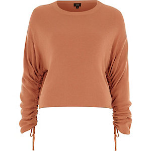 Light orange ruched long sleeve knit top