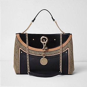 Zwarte gevlochten handtas van stro met verschillende texturen