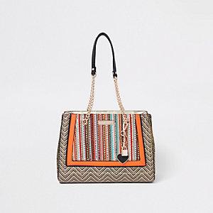 Oranje handtas met geweven paneel en bedel