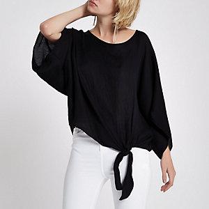 Zwart ruimvallend T-shirt met knoop bij de zoom