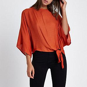 Oranje ruimvallend T-shirt met knoop bij de zoom