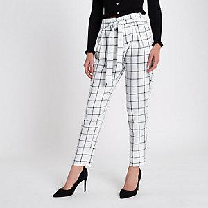 Pantalon fuselé à carreaux blanc avec ceinture à nouer