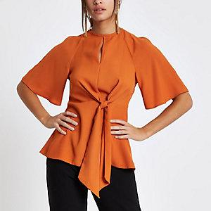 Oranje ruimvallende blouse met strik voor