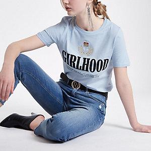 Lichtblauwe top met geborduurd 'girlhood'-embleem