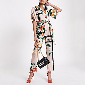 Beige jumpsuit met tropische print, overslag en strikceintuur