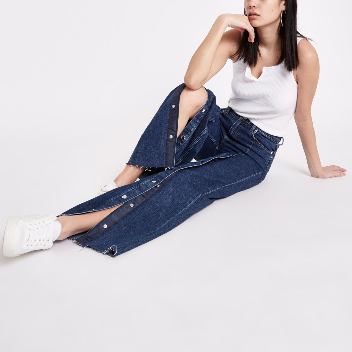 Blauwe jeans met wijde pijpen en drukkers voorop