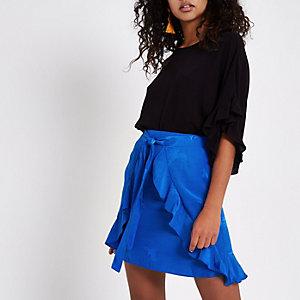 Mini jupe portefeuille bleue en jacquard nouée sur l'avant