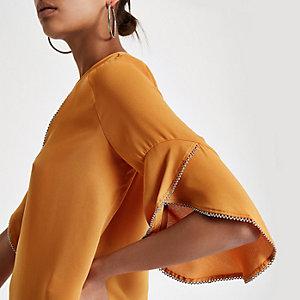 Donkeroranje blouse met ruches en kralenborduursel