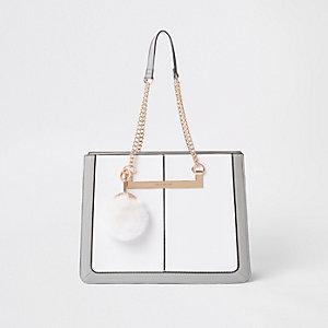 Witte handtas met schakels aan handvat en pompons