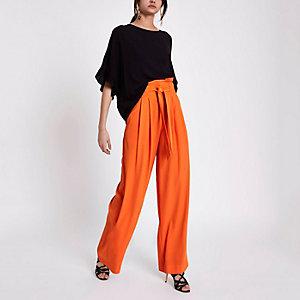 Oranje broek met wijde pijpen en geplooide taille