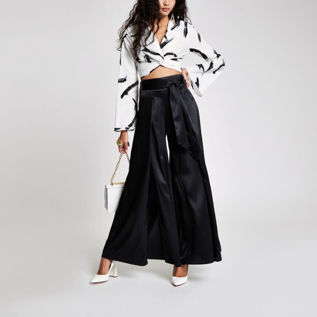 Zwarte broek met wijde pijpen, split en strikceintuur
