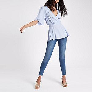 Blauwe blouse met korte mouwen en strikceintuur