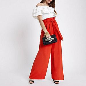 Rode broek met wijde pijpen en strikceintuur