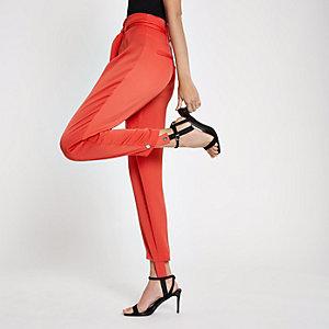 Rode broek met bandjes onder de voet en ceintuur