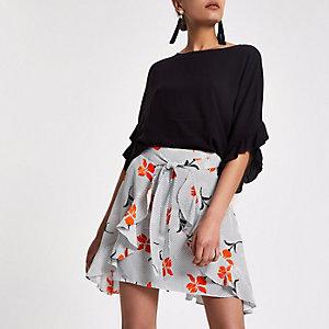 Mini-jupe façon portefeuille à pois et fleurs noire nouée devant
