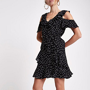 Mini robe à pois noire à épaules dénudées et volant