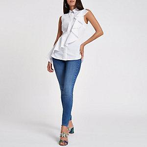 Chemise blanche sans manches bordée de volants