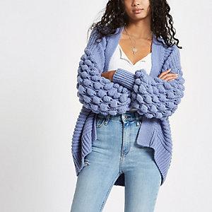 Blaue Strickjacke mit Bommeln